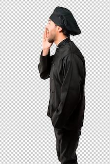 Chef-kok man in zwart uniform schreeuwen met mond wijd open voor de laterale en aankondiging van iets