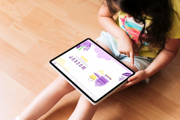 Chica de alta vista usando una maqueta digital de tableta