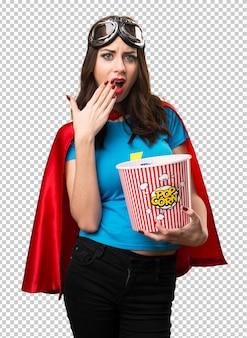 Chica bonita superhéroe comiendo palomitas de maíz