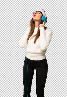 Chica celebrando las fiestas navideñas escuchando música con auriculares.