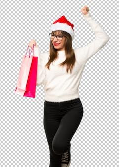 Chica celebrando las fiestas navideñas con muchas bolsas de compras