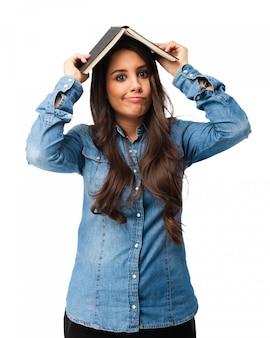 Chica divertida cubriendo su cabeza con un libro