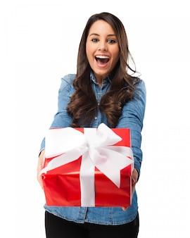 Chica emocionada sujetando un regalo con un lazo blanco