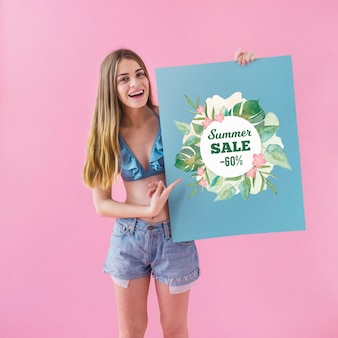 Chica enseñando cartel de rebajas de verano