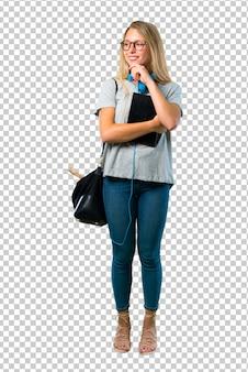 Chica estudiante con gafas de pie y mirando a un lado con la mano en la barbilla