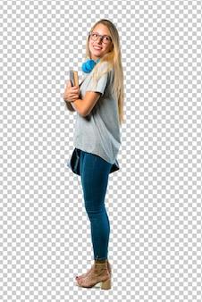 Chica estudiante con gafas en posición lateral mientras mira por encima del hombro con una sonrisa