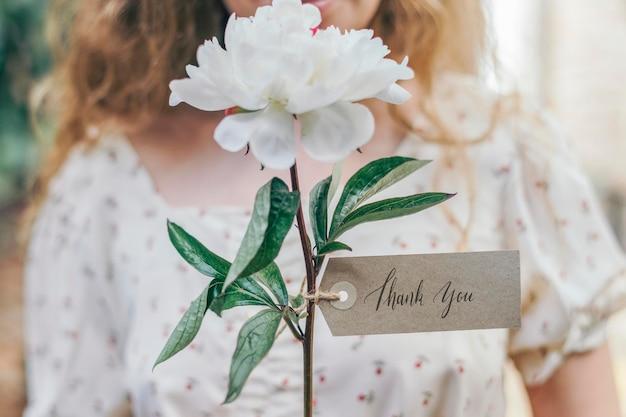 Chica con una flor blanca de snowboard paeonia y una tarjeta de maqueta