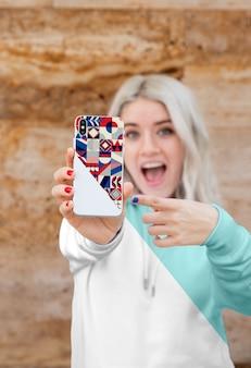 Chica con hoddie apuntando al móvil