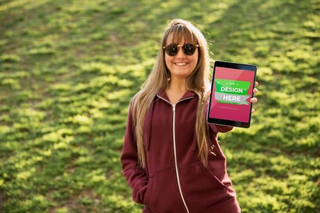 Chica joven atractiva que sostiene una tableta