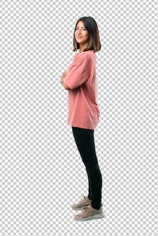 Chica joven con camisa rosa manteniendo los brazos cruzados en posición lateral mientras sonríe