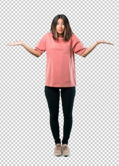 Chica joven con camisa rosa que tiene dudas y con confundir expresión de cara
