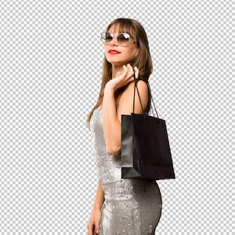 Chica joven con gafas de sol y con bolsas de compras