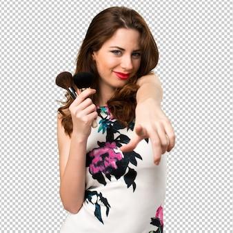 Chica joven hermosa con el cepillo del maquillaje que señala al frente