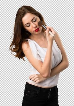 Chica joven hermosa con el cepillo del maquillaje