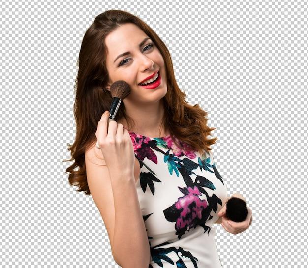 Chica joven hermosa feliz con el cepillo del maquillaje