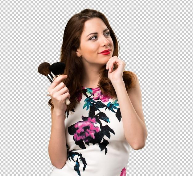 Chica joven hermosa feliz con el pensamiento del cepillo del maquillaje