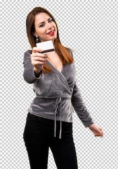 Chica joven hermosa que sostiene una tarjeta de crédito