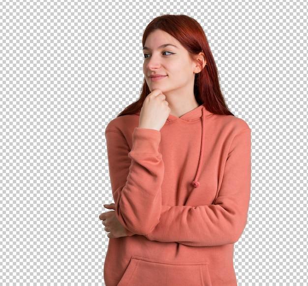 Chica joven pelirroja con sudadera rosa de pie y mirando hacia el lado con la mano en el mentón
