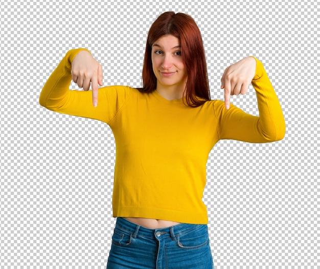 Chica joven pelirroja con suéter amarillo apuntando hacia abajo con los dedos