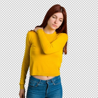Chica joven pelirroja con suéter amarillo que sufre de dolor en el hombro por haber hecho un esfuerzo