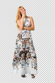 Chica joven rubia en un vestido del verano que se coloca y que piensa una idea mientras que mira para arriba