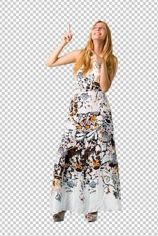 Chica joven rubia en un vestido de verano que señala con el dedo índice una gran idea y mirando hacia arriba