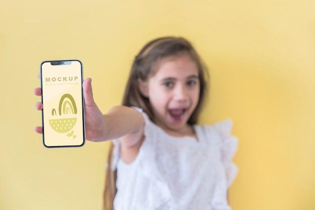 Chica joven sosteniendo teléfono con maqueta