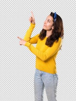 Chica joven con suéter amarillo y pañuelo azul en la cabeza apuntando con el dedo índice