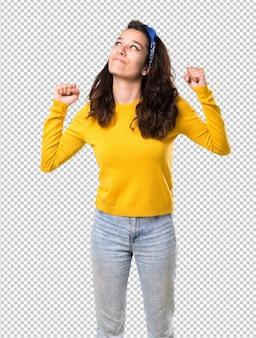 Chica joven con suéter amarillo y pañuelo azul en la cabeza celebrando una victoria en posición de ganador