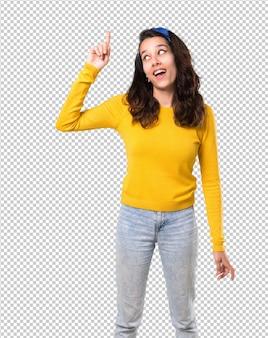 Chica joven con suéter amarillo y pañuelo azul en la cabeza con la intención de darse cuenta de la solución