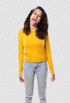 Chica joven con suéter amarillo y pañuelo azul en la cabeza mostrando la lengua en la cámara
