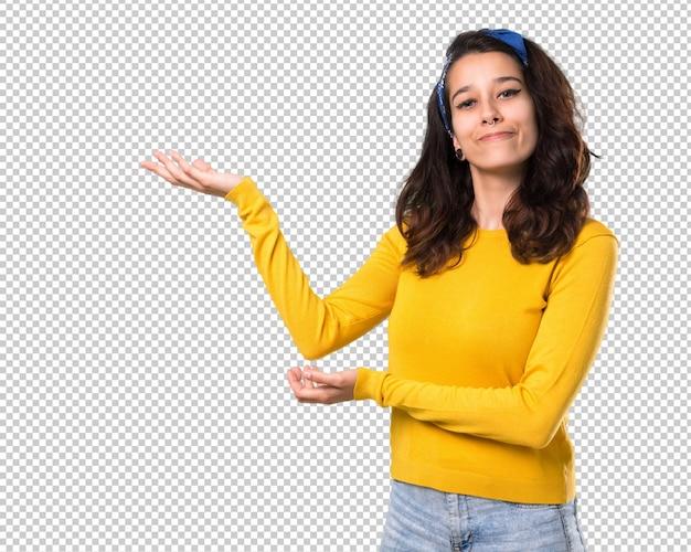 Chica joven con suéter amarillo y pañuelo azul en su cabeza extendiendo las manos