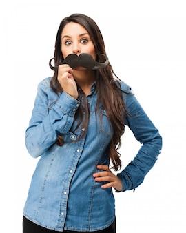 Chica jugando con un bigote falso