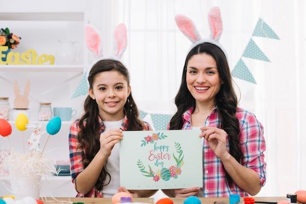 Chica y madre con maqueta de tarjeta en pascua