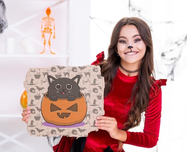 Chica mostrando tarjeta con calabaza tallada y gato