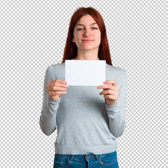 Chica pelirroja joven sosteniendo un cartel blanco vacío para insertar un concepto