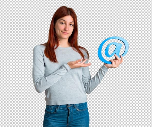 Chica pelirroja joven sosteniendo el icono de punto com