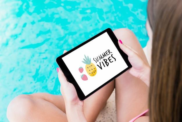 Chica presentando mockup de tableta al lado de piscina