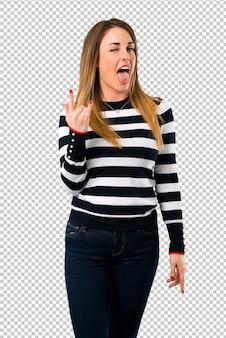 Chica rubia que muestra la lengua en la cámara con aspecto divertido