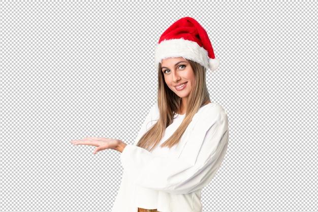 Chica rubia con sombrero de navidad extendiendo las manos a un lado para invitar a venir