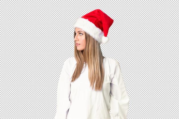 Chica rubia con sombrero de navidad mirando hacia un lado