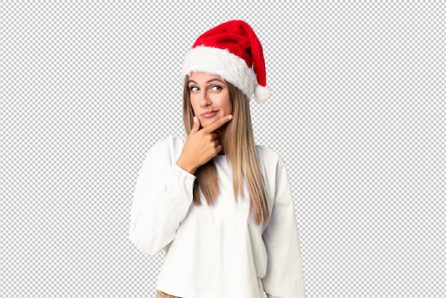 Chica rubia con sombrero de navidad pensando en una idea
