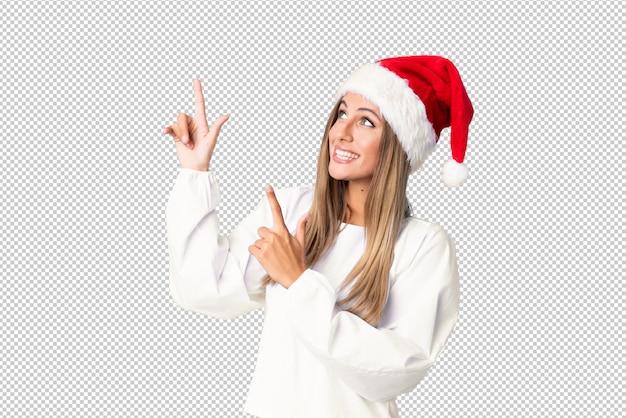 Chica rubia con sombrero de navidad señalando con el dedo índice una gran idea