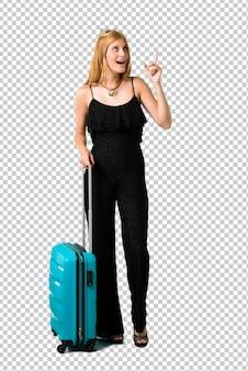 Chica rubia viajando con su maleta de pie y pensando una idea apuntando el dedo hacia arriba