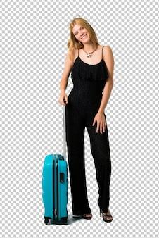 Chica rubia viajando con su maleta de pie y pensando una idea mientras mira hacia arriba