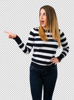 Chica rubia youn apuntando el dedo hacia un lado y presentando un producto