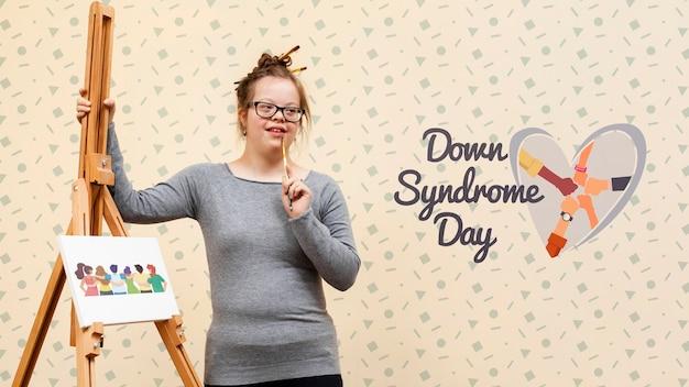 Chica con síndrome de down posando con maqueta de lona