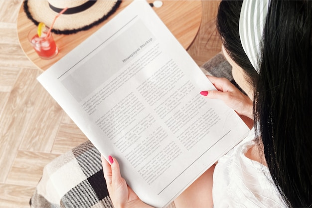 Chica en el sofá leyendo una maqueta de periódico