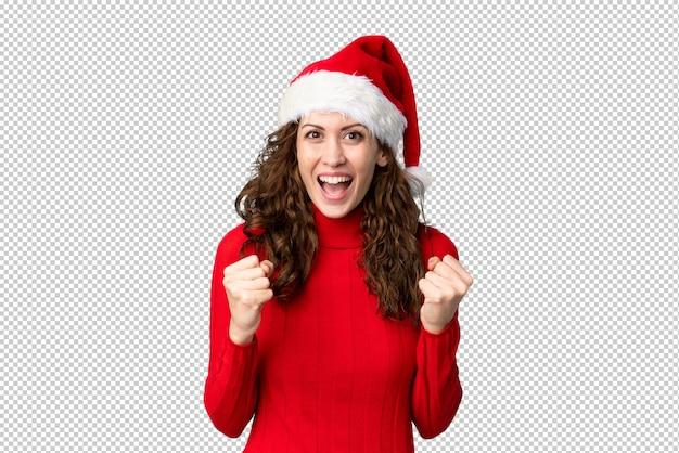 Chica con sombrero de navidad celebrando una victoria