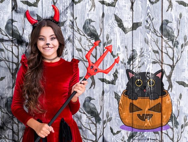 Chica sosteniendo el tridente del diablo cerca de una calabaza animada y un gato